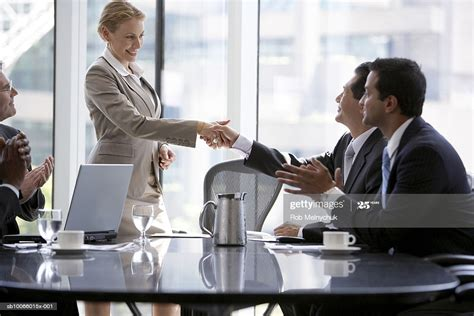 Man And Woman Shaking Hands During Business Meeting High